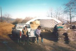 Two people on a pickup truck in front of a Cheviot sheep polytunnel from McGregor Polytunnels